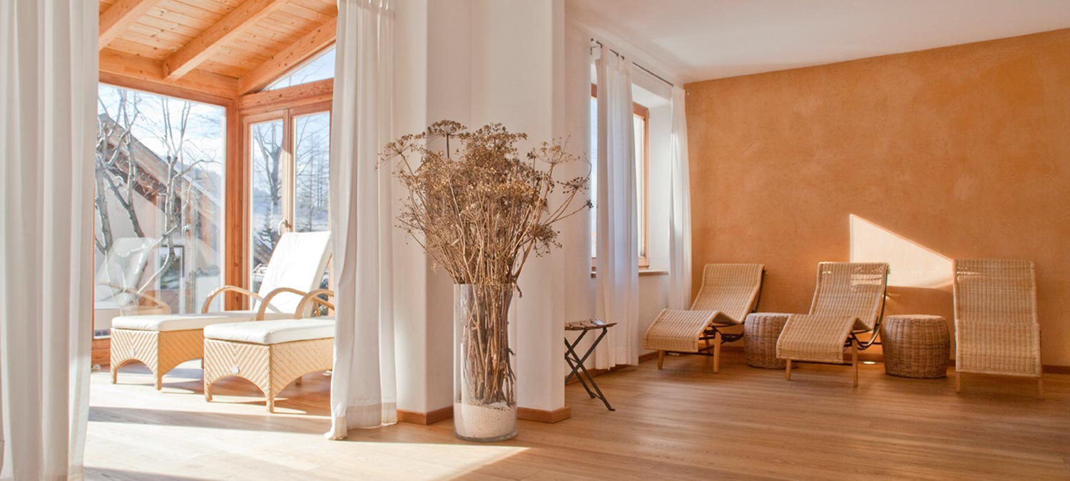 Wellness area with wicker beds, large bright windows, white curtains and potted vase with dry flowers in our 3-star wellness hotel in Sesto Pusteria