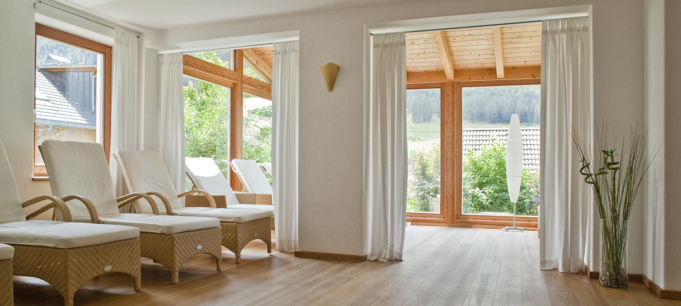 The elegant wellness area of the Hotel Strobl with wicker beds, white curtains and large bright windows