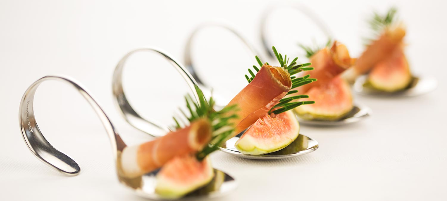 Tasty fingerfood composed of fresh fig, a slice of South Tyrolean speck and sprig of spruce, served on a special silver spoon