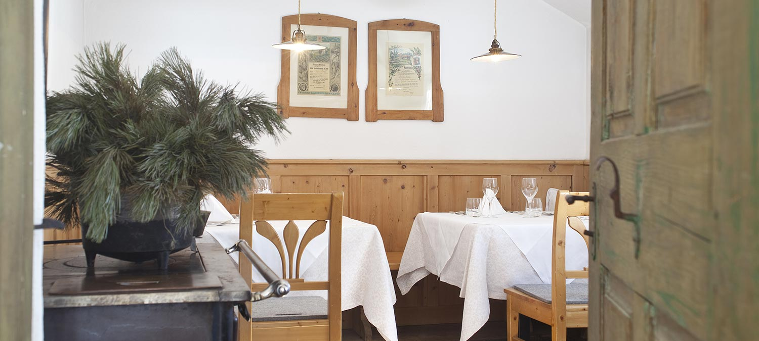 A corner of the dining room of the Hotel Strobl in Sesto with wooden furniture, antique paintings, mugo pine branches above a wood stove and two elegantly decorated tables