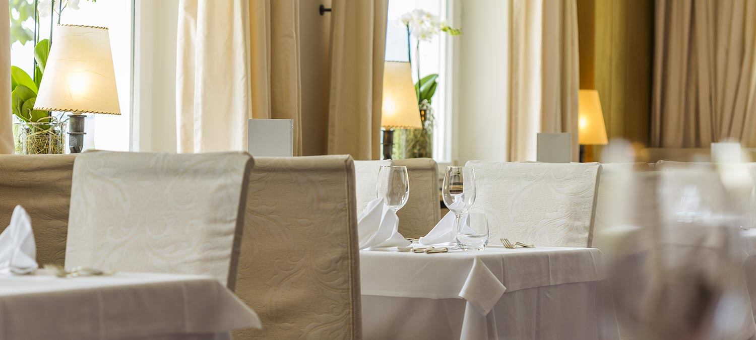 Detail of a table in our hotel's dining room in Sesto Pusteria with white tablecloth, cream-coloured chairs and matching curtains
