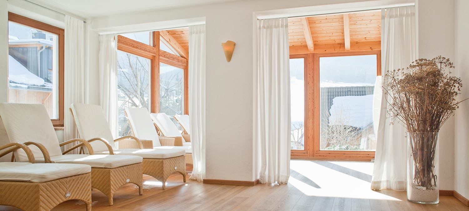 Very bright wellness centre with large windows and wicker beds for a relaxing holiday in Sesto in Val Pusteria