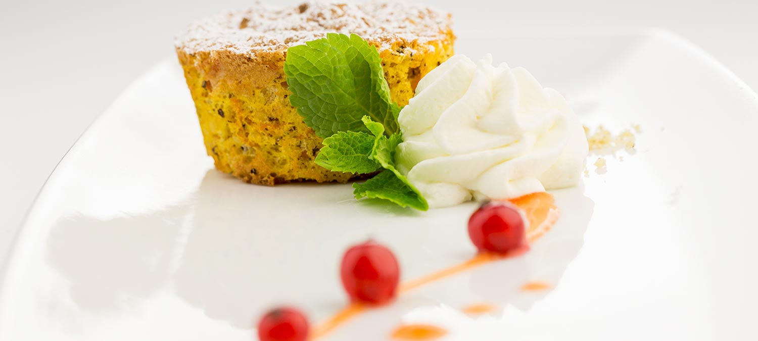 Detail on a carrot pie decorated with mint leaves, whipped cream and cherries