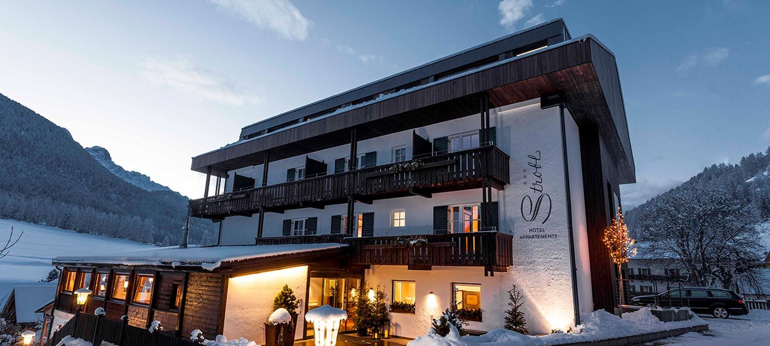 Facade of the Hotel Strobl in Sesto in winter, with the windows illuminated and in the background meadows and snow-covered woods
