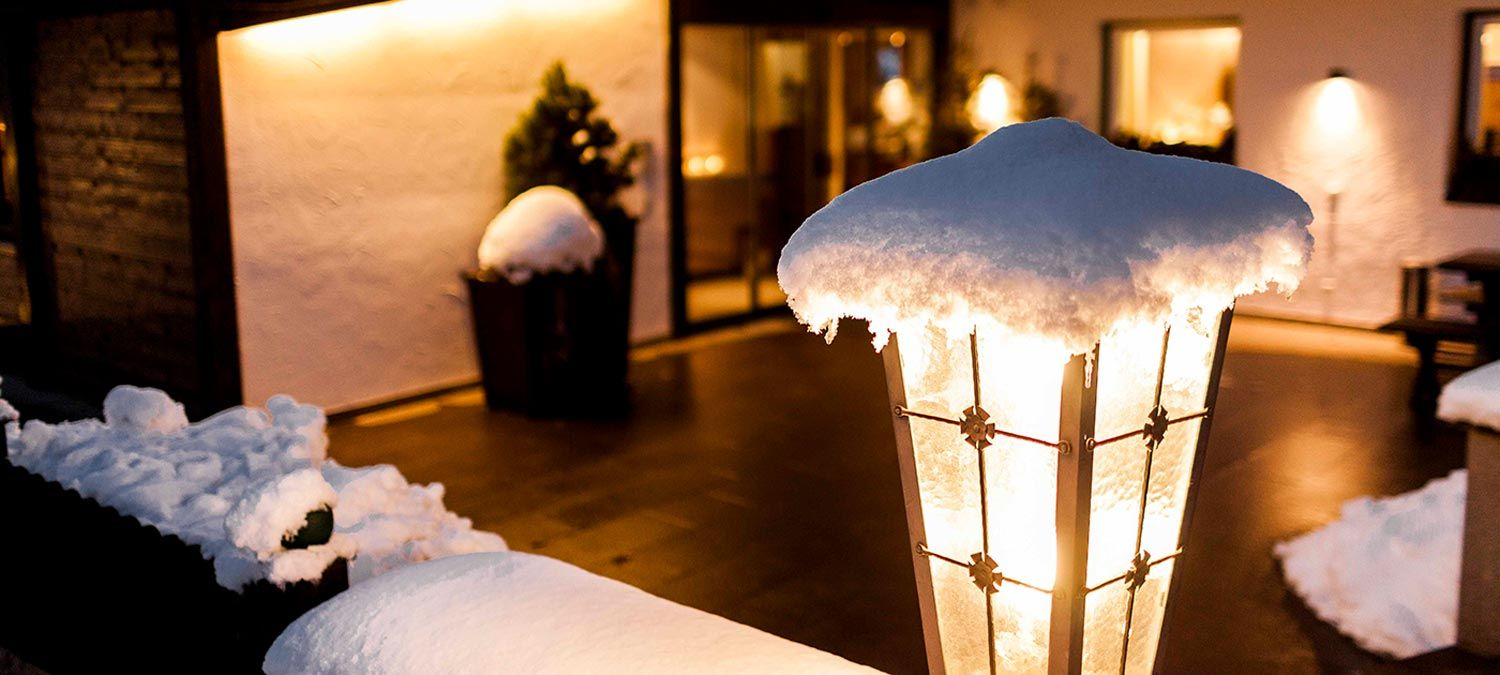 Detail of a snow-covered wrought iron lamp in front of Hotel Strobl