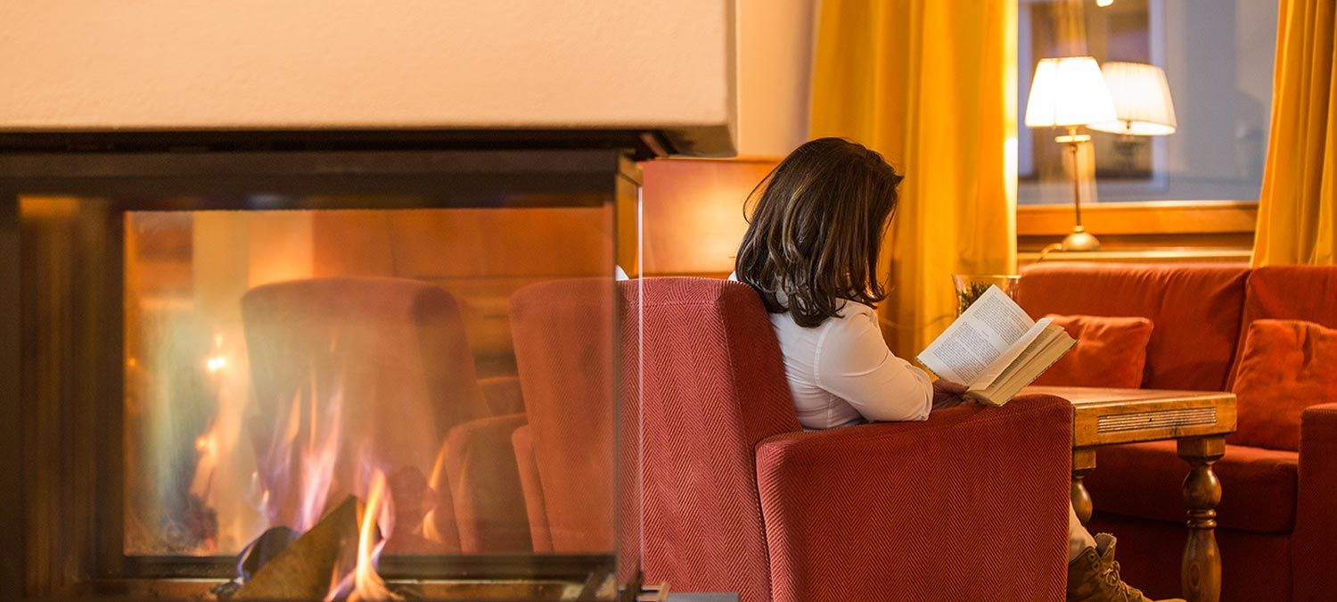 A woman reads a book in front of the fireplace sitting on the soft red armchair of our traditional South Tyrolean stube