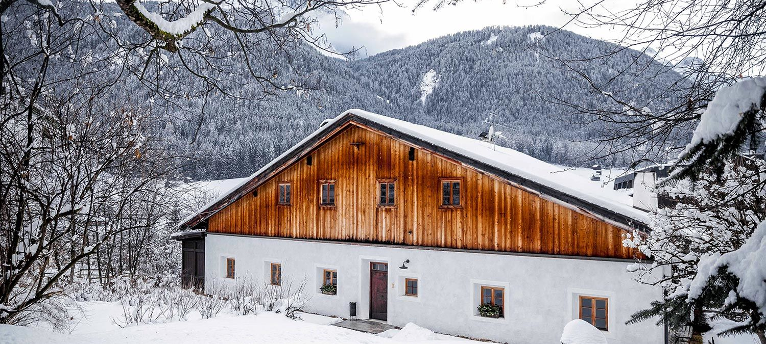A typical house in Sesto in Val Pusteria during the winter, with snow-covered mountains and woods in the background