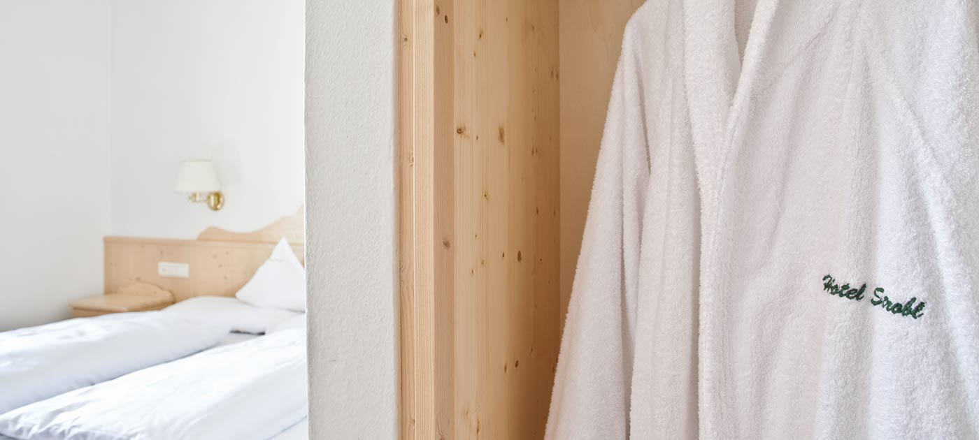Detail of a white cotton bathrobe hanging in one room of our holiday apartments in Sesto Pusteria furnished in spruce with double bed in the background