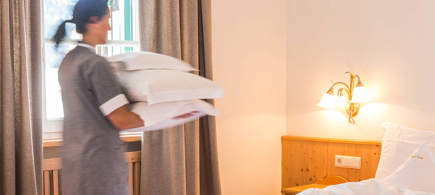 Waitress that prepares the beds for the guests of Hotel Strobl in Sesto in Val Pusteria